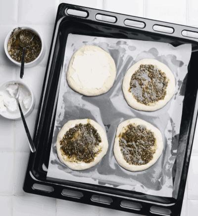 طرز تهیه نان زعتر لبنانی با پنیر خامهای<br> <br> <br> یکی از ادویههای معروف در کشورهای عربی، «زعتر» نام دارد که مخلوطی از گیاهان خوش عطر و پرخاصیت است. <br> <br> تاریخچهی این ادویه، به قرنهای بسیار دور میرسد و در بسیاری از غذاهای معروف از آن استفاده میشود. <br> <br> با مستر آشپز همراه باشید تا تهیه نان زعتر را به شما آموزش دهیم <br> که یکی از محبوبترین پیش غذاهای عربی محسوب میشود.<br> <br> <br> مواد لازم<br> <br> 🔹آرد نان فانتزی: دو و نیم پیمانه<br> 🔹پنیر خامهای: ۱۵۰ گرم<br> 🔹روغن زیتون: نصف پیمانه<br> 🔹شکر: ۱ قاشق چایخوری<br> 🔹مایهی خمیر فوری: یک و نیم قاشق چایخوری<br> 🔹زعتر: ۳ قاشق غذاخوری<br> 🔹نمک: ۱ قاشق غذاخوری<br> 🔹آب ولرم: یک و نیم پیمانه<br> <br> <br> طرز تهیه نان زعتر لبنانی با پنیر خامهای<br> <br> <br> طرز تهیه<br> <br> ۱.مایهی خمیر را با نصف پیمانه آب ولرم و شکر مخلوط کنید و درب ظرف را بگذارید. <br> در صورتی که مایهی خمیر شما سالم و تازه باشد، بعد از ۱۰ دقیقه باید مانند تصویر کف کند.<br> <br> ۲.باقیماندهی آب ولرم را با مایهی خمیر آماده شده، آرد و نمک در یک ظرف با هم مخلوط کنید. <br> دقت کنید که میزان آرد با توجه به میزان جذب رطوبت آن متفاوت است؛ <br> پس آرد را با احتیاط و تا جایی که خمیر شکل بگیرد اضافه کنید.<br> <br> ۳.وقتی خمیرتان به حالتی رسید که شکل گرفته اما هنوز به دست میچسبد، <br> یک سوم از روغن زیتون را کم کم به آن اضافه کنید و ۱۰ دقیقه ورز دهید. <br> در صورتی که خمیر هنوز چسبندگی زیادی داشت، کمی آرد روی آن بپاچید <br> و با ورز دادن و کوبیدن خمیر روی میز کار، چسبندگی آن را از بین ببرید و آن را کشدار کنید.<br> <br> ۴.خمیر آماده شده را مانند تصویر، در یک کاسهی چرب شده قرار دهید و روی آن را با سلفون بپوشانید <br> و در جای گرم قرار دهید تا حدود ۱ تا ۲ ساعت استراحت کند.<br> <br> ۵.زعتر را با مابقی روغن زیتون مخلوط کنید.<br> <br> ۶.بعد از ۲ ساعت، خمیر شما پف میکند و حجم آن ۲ برابر میشود. <br> آن را از ظرف خارج کنید و ۳ دقیقهی دیگر ورز دهید.<br> <br> ۷.حالا خمیر را به ۸ چانه تقسیم کنید. کف سینی فر را کمی چرب کنید و کاغذ روغنی را روی آن قرار دهید. <br> حالا هر چانه خمیر را روی کاغذ روغنی چرب شده، به قطر ۱ سانتیمتر پهن کنید. <br> روی هر چانه، مقداری پنیر خ